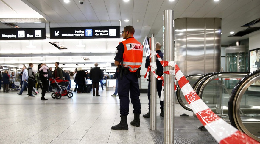 A police officer stands next to stairs at the closed entrance for check-in one and two at Zurich airport in Kloten December 15, 2014. Zurich airport was partially closed on Monday evening after receiving an unspecified threat, an airport spokeswoman said. REUTERS/Arnd Wiegmann (SWITZERLAND - Tags: TRANSPORT CRIME LAW)