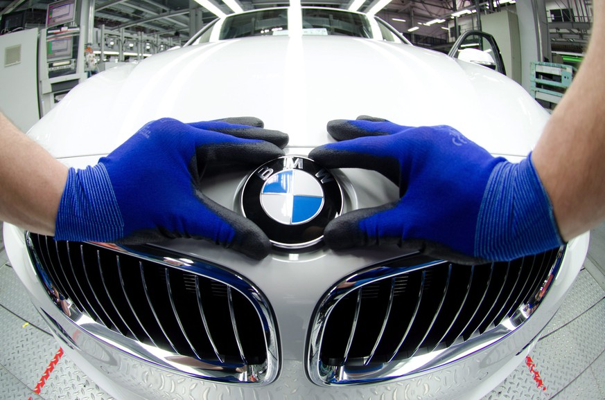epa04475551 (FILE) A file photo dated 07 March 2012 showing an employee attaching a BMW logo onto the hood of a new car at the factory in Regensburg, Germany. Luxury carmaker BMW reported 04 November 2014 a surprise fall in third-quarter profit, despite strong demand in Asia helping drive a solid gain in group sales. Net profit dropped to 1.31 billion euros (1.63 billion dollars) in the three months to September, from 1.33 billion in the same period last year. Analysts had expected Q3 profits to rise to 1.36 billion euros. The Munich-based company pointed to a higher tax bill as having hit its quarterly profits and confirmed its business outlook for the full-year. BMW expects to post a 'significant' increase in pretax profit from last year's 7.913 billion euros and to deliver more than 2 million cars in 2014 as it attempts to remain ahead of rival premium carmakers Audi and Mercedes Benz.  EPA/ARMIN WEIGEL *** Local Caption *** 00000403160589