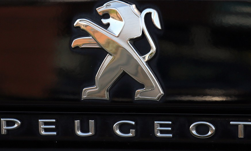 FILE - In this Oct. 31, 2019, file photo, a Peugeot logo pictured on a car in Bayonne, southwestern France. Fiat Chrysler Automobiles and PSA Peugeot announced Wednesday, Dec. 18, 2019, that their boards signed a binding deal to merge the two automakers, creating the world's fourth-largest auto company. (AP Photo/Bob Edme, File)