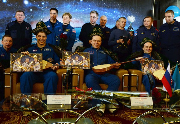 epa04119795 (L-R, front) Wearing traditional Kazakh costumes US astronaut Michael Hopkins sits together with Russia's cosmonauts Oleg Kotov and Sergey Ryazanskiy, as they attend a press conference in Karaganda, Kazakhstan, 11 March 2014, some hours after their landing aboard Soyuz TMA-10M capsule. US astronaut Michael Hopkins together with two Russia's cosmonauts, Oleg Kotov and Sergey Ryazanskiy, landed safely in the Kazakh steppe aboard a Russian Soyuz capsule after a stay of over five months aboard the International Space Station.  EPA/VASILY MAXIMOV/POOL