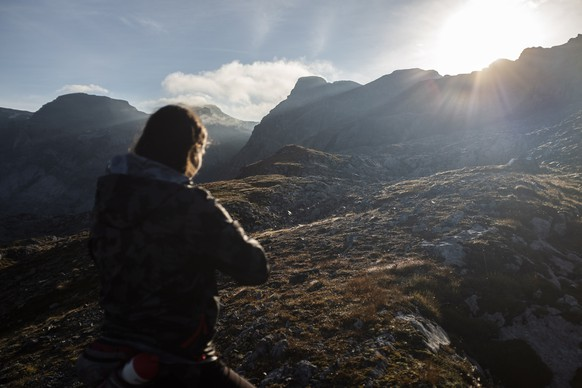 epa08667512 A woman looks into the sunrise while hiking on an alpine trail at Panixerpass in Elm, Switzerland, 13 September 2020.  EPA/GIAN EHRENZELLER