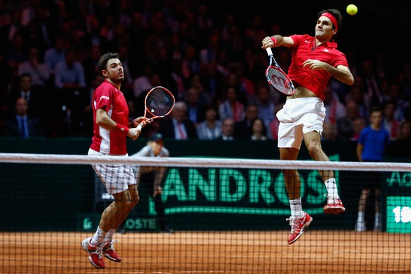 LILLE, FRANCE - NOVEMBER 22:  Roger Federer of Switzerland and Stanislas Wawrinka of Switzerland in action against Richard Gasquet of France and Julien Benneteau of France in the doubles during day two of the Davis Cup Tennis Final between France and Switzerland at the Stade Pierre Mauroy on November 22, 2014 in Lille, France.  (Photo by Julian Finney/Getty Images)
