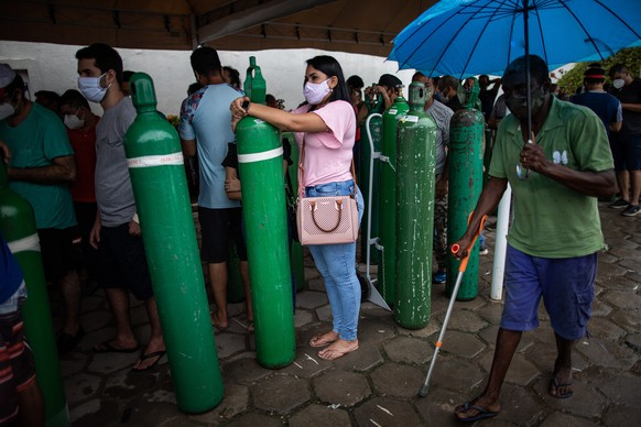 epa08949847 Relatives of patients infected with Covid-19 wait for hours since early in the morning to refill their oxygen cylinders at the Carboxi company, in Manaus, Amazonas, Brazil, on 19 January 2021. An air, river and terrestrial fleet began on 19 January the distribution of vaccines against covid in the collapsed Brazilian state of Amazonas, vaccines that will have to reach the most distant villages, a tremendous task due to the difficulties imposed by the largest jungle on the planet.  EPA/RAPHAEL ALVES
