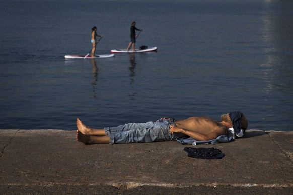 A man rests next to the beach during a hot summer day in Barcelona, Spain, Friday, Aug. 3, 2018. Hot air from Africa is bringing a heat wave to Europe, prompting health warnings about Sahara Desert dust and exceptionally high temperatures that could peak at 47 degrees Celsius (117 Fahrenheit) in Spain and Portugal. (AP Photo/Emilio Morenatti)