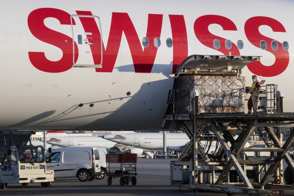 Workers unload boxes containing facial masks and medical syringe pump from China from an aircraft Boeing 777 of Swiss International Air Lines at the Zurich Aeroport, in Zurich, Switzerland, Monday, April 27, 2020.  (KEYSTONE/Ennio Leanza)