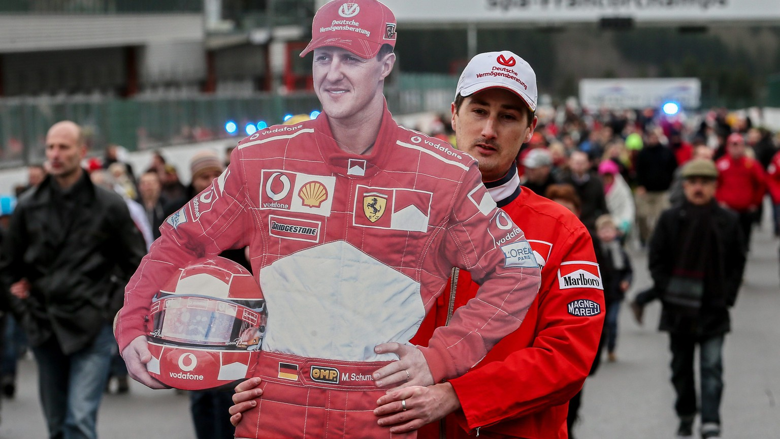 epa04042757 A fan of German Formula One legend Michael Schumacher carries a life-size cardbord cutout of his idol on the Spa Fancorchamp racetrack, Belgium, 26 January 2014. Thousands of fans coming from Belgium, Germany, France and the Netherlands gathered on the race course in Spa where Schumacher won his first Formula One race in 1992. The 45-year-old seven-time Formula One world champion has been in a medically induced coma in a Grenoble hospital since a skiing accident in France. Schumacher's condition after two operations is described by doctors as critical but stable.  EPA/OLIVIER HOSLET