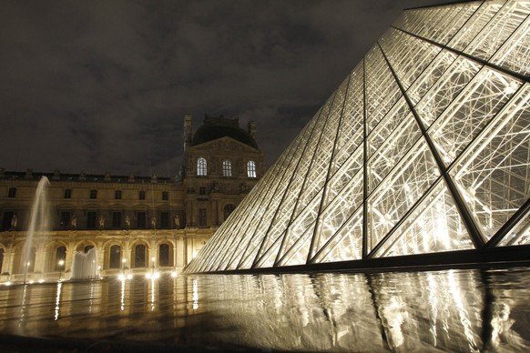 New external lighting are inaugurated at the Louvre, the world's most popular art museum, at the Pyramid, the three pyramidions and the Colbert pavilion of the Louvre, with the warm glow of new LED lighting , Tuesday Dec. 6, 2011 in Paris. (AP Photo/Christophe Ena)