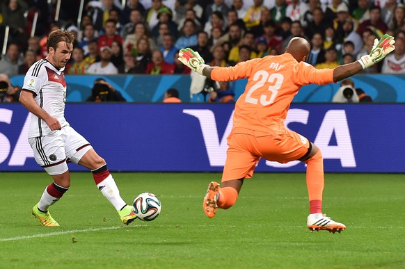 Germany's forward Mario Goetze (L) tries to score a goal as Algeria's goalkeeper Rais Mbohli defends during a Round of 16 football match between Germany and Algeria at Beira-Rio Stadium in Porto Alegre during the 2014 FIFA World Cup on June 30, 2014.  AFP PHOTO / KIRILL KUDRYAVTSEV