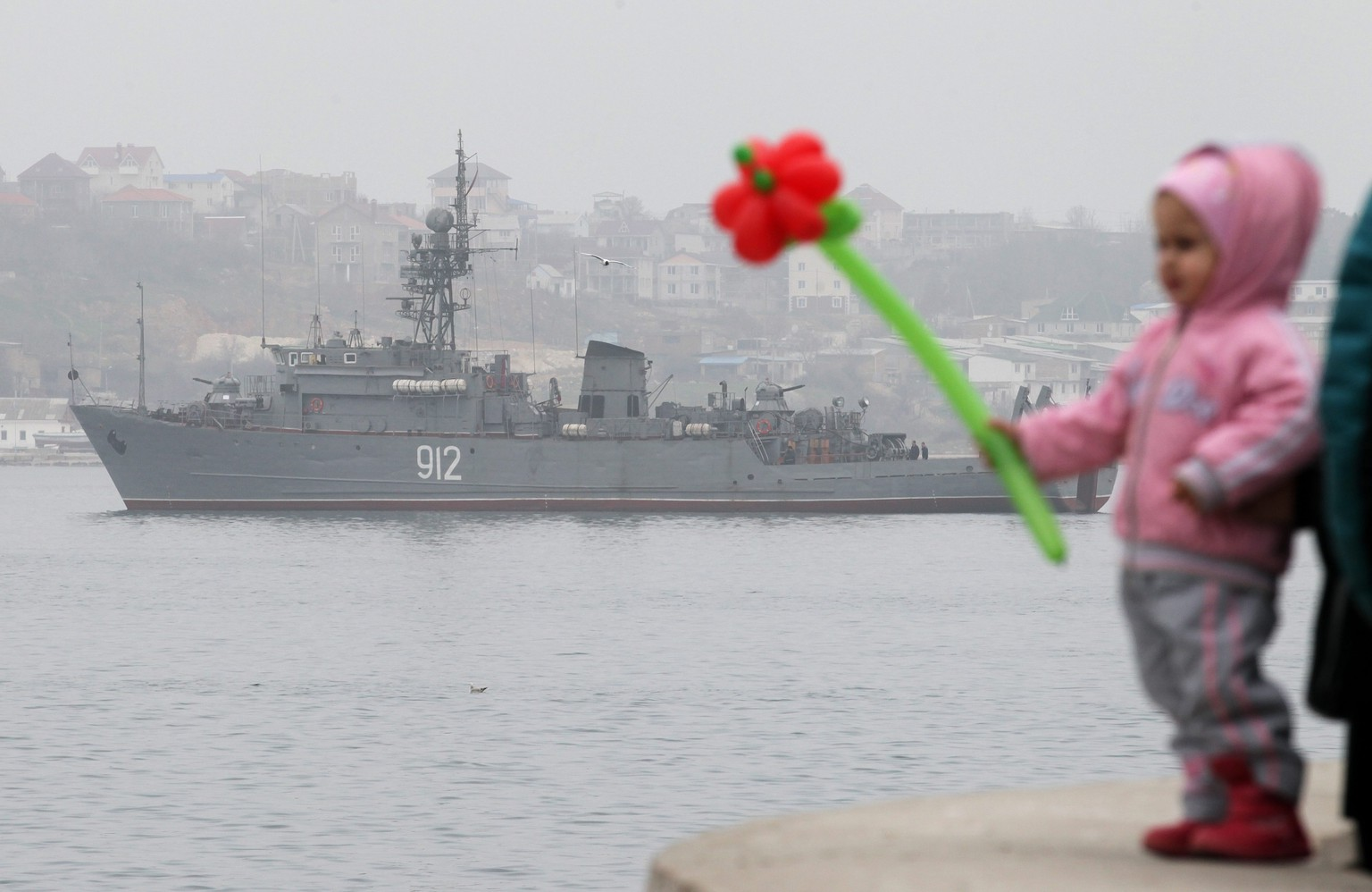 epa04115028 A child holds a flower as a Russian Navy ship, the minesweeper 'Turbinist', patrols the harbor of Sevastopol, Crimea, Ukraine, 08 March 2014. The USA and European Union have threatened sanctions against Moscow over the military standoff in the strategic Crimean peninsula, and are urging Russia to pull back its forces in the region and allow in international observers and human rights monitors. Crimea, which has a majority ethnic Russian population, is strategically important to Russia as the home port of its Black Sea Fleet.  EPA/ZURAB KURTSIKIDZE