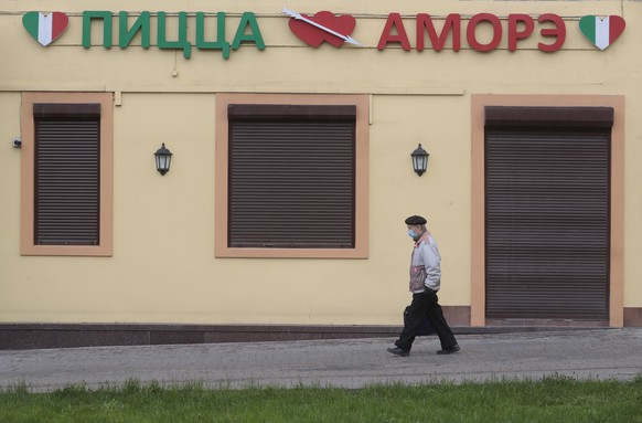 epa08439137 An elderly Russian man passes by a closed  Italian pizzeria in Moscow, Russia, 23 May 2020. All restaurants, shops except food stores, parks and playand sport grounds and other places attracting people stay closed for visitors until at least till 31 May.  EPA/SERGEI CHIRIKOV