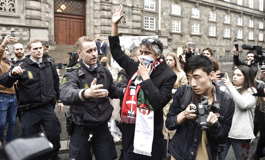 epa07012630 French-Algerian businessman, Rachid Nekkaz (C), is asked by to police officers to step down from the main entrance in front of the Danish Parliament Christiansborg in Copenhagen, Denmark, 11 September 2018. Nekkaz is in Copenhagen to fulfill his promise to pay persons who has been fined for violating the ban of masking with niqab in public areas. So far nobody in Denmark have been fined and therefore there was no fines to pay.  EPA/MADS CLAUS RASMUSSEN  DENMARK OUT
