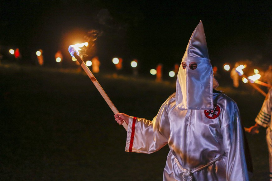 epa05275310 A picture made available on 24 April 2016 shows Pro-white rights organizations the neo-nazi National Socialist Movement and Ku Klux Klan groups participate in a cross and swastika burning in Temple, Georgia, USA, 23 April 2016. The ceremony was held after a day of rallies at Stone Mountain and Rome, Georgia, and to show successful collaboration agreements between the NSM and KKK, two white extremist groups.  EPA/ERIK S. LESSER