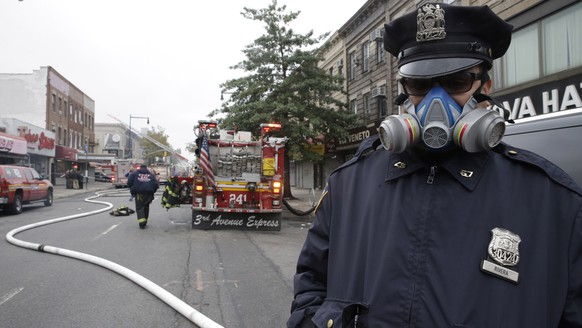 A police officer wears a mask while working near the scene of an explosion in the Brooklyn borough of New York, Saturday, Oct. 3, 2015. Firefighters in New York say one person is dead and three more have been injured in an apparent explosion and fire at a three-story building in the Borough Park neighborhood. (AP Photo/Mary Altaffer)
