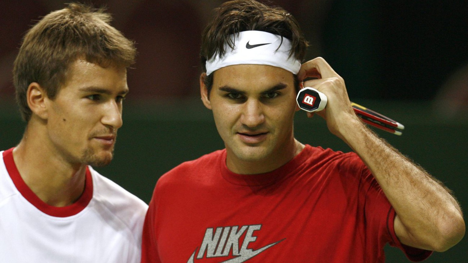 World number one tennis player Roger Federer of Switzerland, right, and teammate Marco Chiudinelli, left, speak together during the first training session before their Davis Cup World Group Play-offs 1st round against Serbia, in Geneva, Switzerland, on Monday, September 18, 2006. (KEYSTONE/Laurent Gillieron)