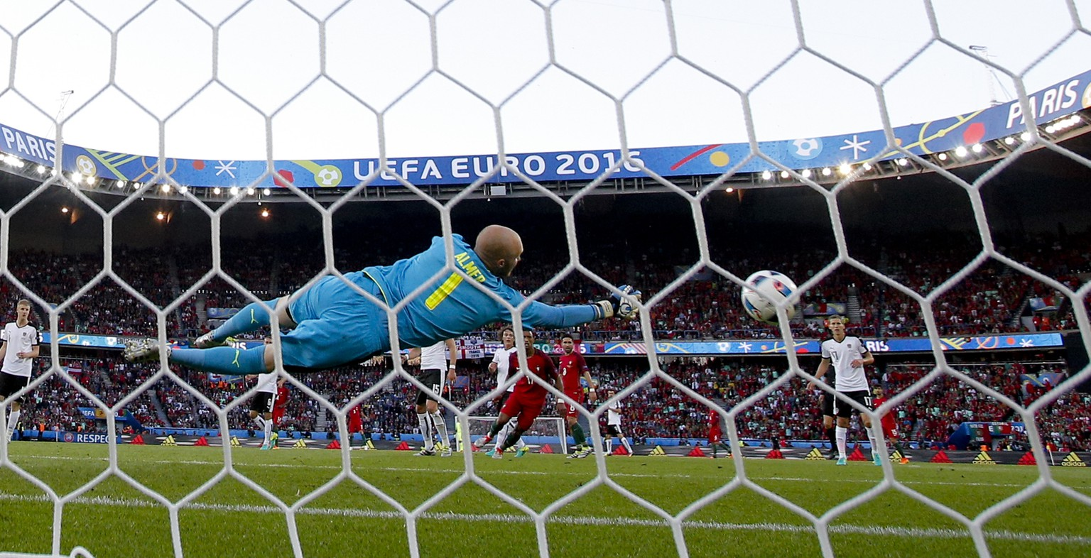 Austria goalkeeper Robert Almer dives for the ball during the Euro 2016 Group F soccer match between Portugal and Austria at the Parc des Princes stadium in Paris, France, Saturday, June 18, 2016. (AP Photo/Christophe Ena)