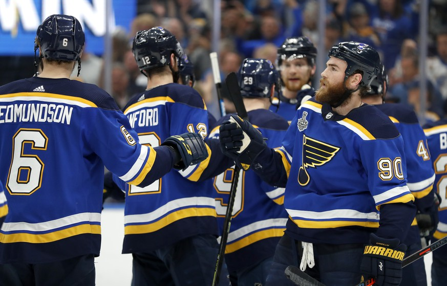 St. Louis Blues center Ryan O'Reilly (90) celebrates with Joel Edmundson (6) after the Blues beat the Boston Bruins in Game 4 of the NHL hockey Stanley Cup Final Monday, June 3, 2019, in St. Louis. O'Reilly scored two goals as the Blues won 4-2 to tie the series 2-2. (AP Photo/Jeff Roberson)