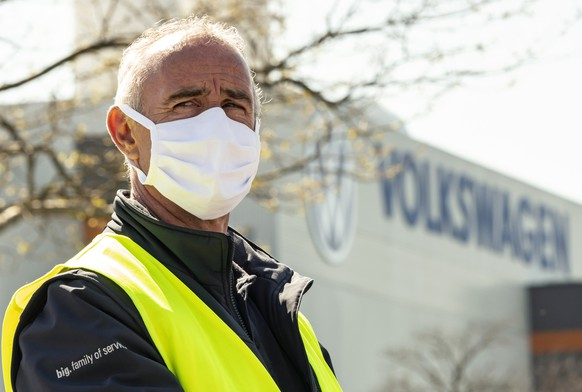An employee wearing a face mask in front of a factory building during the production restart of the plant of the German manufacturer Volkswagen AG (VW) in Zwickau, Germany, Thursday, April 23, 2020. Volkswagen starts with step-by-step resumption of production. The car company are completely converting the plant in Zwickau from 100 percent combustion engine to 100 percent electric. (AP Photo/Jens Meyer)