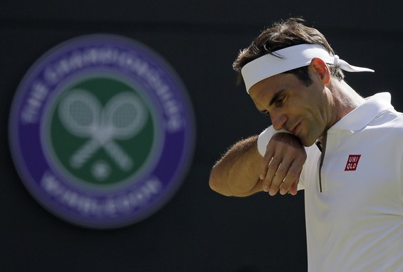Switzerland's Roger Federer wipes his face as he plays Britain's Jay Clarke in a Men's singles match during day four of the Wimbledon Tennis Championships in London, Thursday, July 4, 2019. (AP Photo/Tim Ireland)