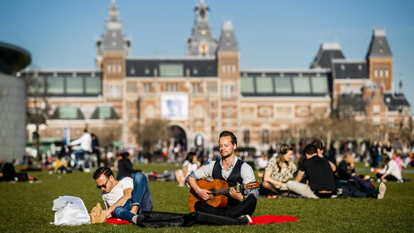 epa07399099 People enjoy the sunny weather on the Museum Square, Amsterdam, The Netherlands, 26 February 2019. Reports state that it is exceptionally warm for the time of year.  EPA/REMKO DE WAAL