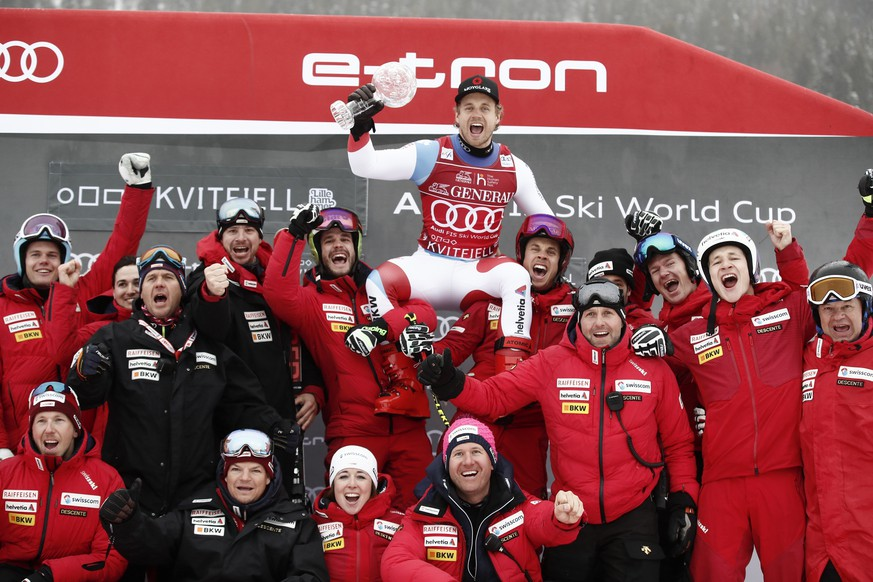 Switzerland's Mauro Caviezel celebrates with his team after winning the alpine ski, men's World Cup super-G discipline title, in Kvitfjell, Norway, Sunday, March 8, 2020. (AP Photo/Gabriele Facciotti)