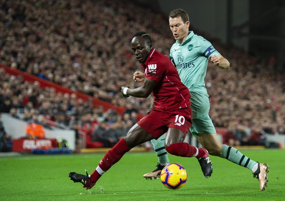epa07253288 Liverpool's Sadio Mane (L) in action with Arsenal's Stephan Lichtsteiner (R) during the English Premier League soccer match between Liverpool and Arsenal at the Anfield in Liverpool, Britain, 29 December 2018.  EPA/PETER POWELL EDITORIAL USE ONLY. No use with unauthorized audio, video, data, fixture lists, club/league logos or 'live' services. Online in-match use limited to 120 images, no video emulation. No use in betting, games or single club/league/player publications