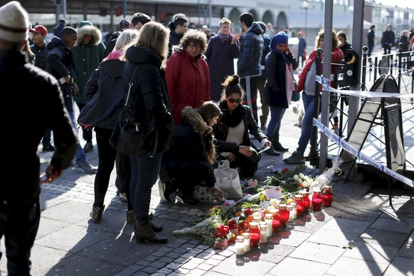 People place flowers at the scene, in Goteborg, Sweden, Thursday, March 19, 2015, a day after a shooting incident. Several people were shot inside a restaurant in the city of Goteborg late Wednesday and at least two of them have died, Swedish police said. Police said in a statement that an automatic weapon is believed to have been used in the shooting. They had no details on any suspects but said several people had been brought in for questioning. (AP Photo/Adam Ihse/TT News Agency) SWEDEN OUT