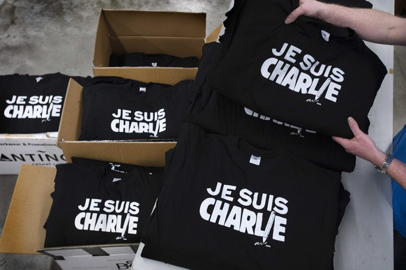 epa04552611 T-shirts are being printed with the text Je suis Charlie (I am Charlie) at the printing house Festa in Langenboom, The Netherlands, 09 January 2014. Those who are interested can pick up the t-shirt, that refers to the attack on the satirical magazine Charlie Hebdo, for free.  EPA/PIROSCHKA VAN DE WOUW