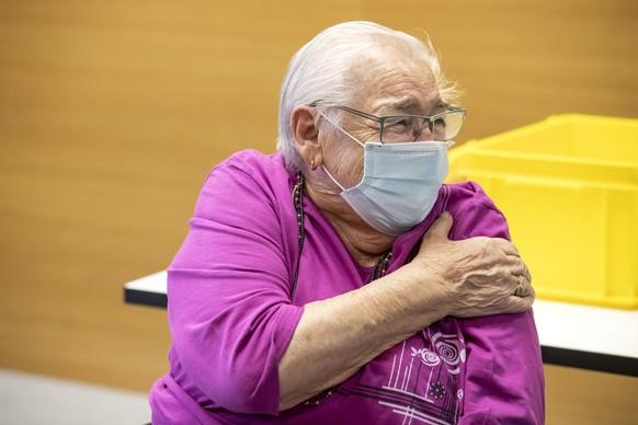 Emmi Zimmerli haelt sich den Oberarm nach der Impfung gegen Covid-19, an ihrem 89. Geburtstag, in einem Altersheim in Gelterkinden am Dienstag, 29. Dezember 2020. Eine mobile Impf-Equipe ist im Einsatz im Kanton Basel-Land. (KEYSTONE/Alexandra Wey)