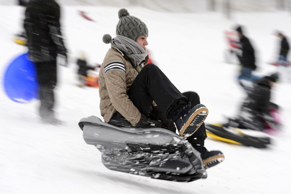 People enjoy sledging in the fresh snow on the Chalet-a-Gobet slope, in Lausanne, Switzerland, Sunday, December 28, 2014. Switzerland experienced the warmest fall and early winter ever recorded in weather statistics. (KEYSTONE/Laurent Gillieron)..