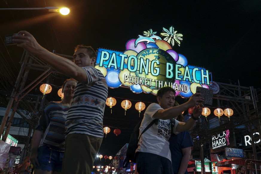 Tourists take selfie on a street near Patong beach in Phuket, Thailand March 19, 2016. With its palm-fringed beaches, Buddhist culture and racy nightlife, Thailand has been the poster child for Asian tourism for decades, attracting a range of visitors from backpackers and adventure-seekers, to families and culture vultures. But dark clouds could be forming even as a record of 32 million tourists are expected this year. REUTERS/Athit Perawongmetha SEARCH