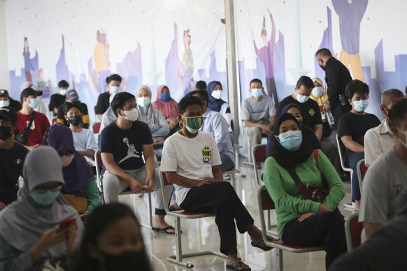 People wait before they receive a shot of the Sinovac vaccine for COVID-19 during a vaccination campaign in Jakarta, Indonesia, Monday, July 12, 2021. (AP Photo/Achmad Ibrahim)