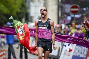 French Yohann Diniz celebrates with a French and a Portugal flag after he crossed the finish line and won the Men's 50km walk at the European Athletics Championships in Zurich on August 15, 2014. Diniz smashed the world record in a time of 3hr 32min 33sec.     AFP PHOTO / MICHAEL BUHOLZER
