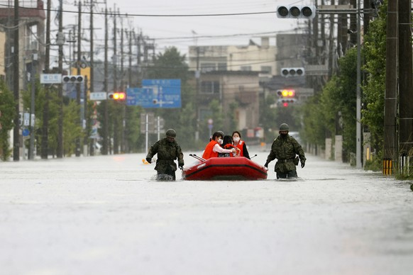 Japan Self Defense Force members rescue residents on a rubber boat on a flooded road hit by heavy rain in Omuta, Fukuoka prefecture, southern Japan Tuesday, July 7, 2020. Rescue operations continued and rain threatened wider areas of the main island of Kyushu. (Koji Harada/Kyodo News via AP)