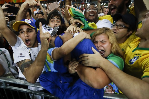 Brazil's Rafaela Silva, centre in blue, celebrates with supporters after winning the gold medal of the women's 57-kg judo competition at the 2016 Summer Olympics in Rio de Janeiro, Brazil, Monday, Aug. 8, 2016. (AP Photo/Markus Schreiber)