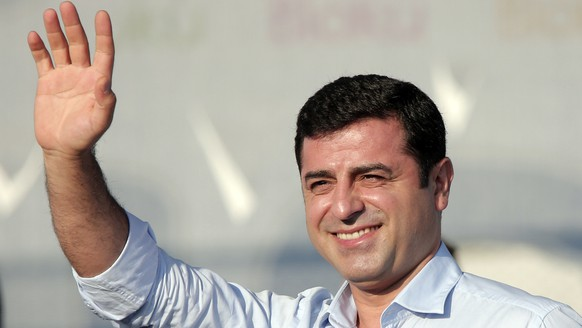 FILE - In this Sunday, Aug. 9, 2015 file photo, Selahattin Demirtas, then leader of the pro Kurdish Democratic Party of Peoples (HDP) waves to people gathered for a pro-peace rally in Istanbul. Demirtas, who has been behind bars since November 2016, is in prison accused of links to outlawed Kurdish rebels and is facing a 142-year sentence on charges of leading a terror organisation. Turkey's weak opposition is scrambling to try and mount a strong challenge against strongman Turkey's President with just nine weeks to prepare for snap elections, scheduled for June 24, 2018. Turkey is switching from a parliamentary system to an executive presidential system that will concentrate increased powers in the hands of the president, following a narrowly approved referendum last year. (AP Photo/Lefteris Pitarakis, File)