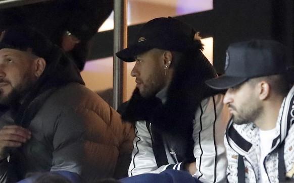 PSG's Neymar, center, watches in the tribune the French League One soccer match between Paris Saint-Germain and Bordeaux at the Parc des Princes stadium in Paris, Saturday, Feb. 9, 2019. (AP Photo/Christophe Ena)