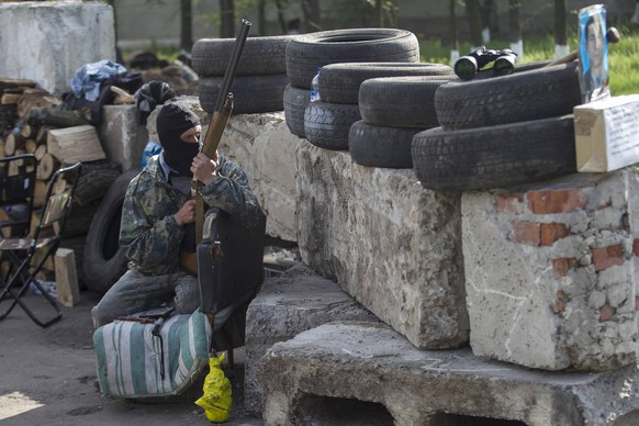 A pro-Russian armed man guards a checkpoint near the town of Slaviansk, east Ukraine May 1, 2014. REUTERS/Baz Ratner (UKRAINE - Tags: POLITICS CIVIL UNREST)