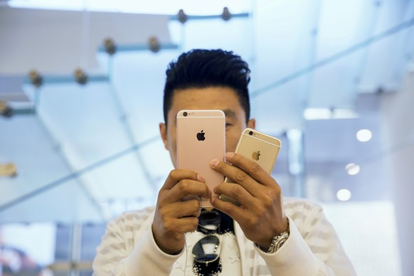 A man takes pictures as Apple iPhone 6s and 6s Plus go on sale at an Apple Store in Beijing, China September 25, 2015. REUTERS/Damir Sagolj/File Photo