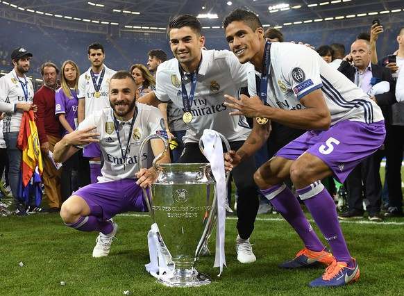 epa06009981 Real Madrid players Karim Benzema (L), Enzo Zidane and Raphael Varane (R) celebrate with the trophy after the UEFA Champions League final between Juventus FC and Real Madrid at the National Stadium of Wales in Cardiff, Britain, 03 June 2017. Real Madrid won 4-1.  EPA/ANDY RAIN