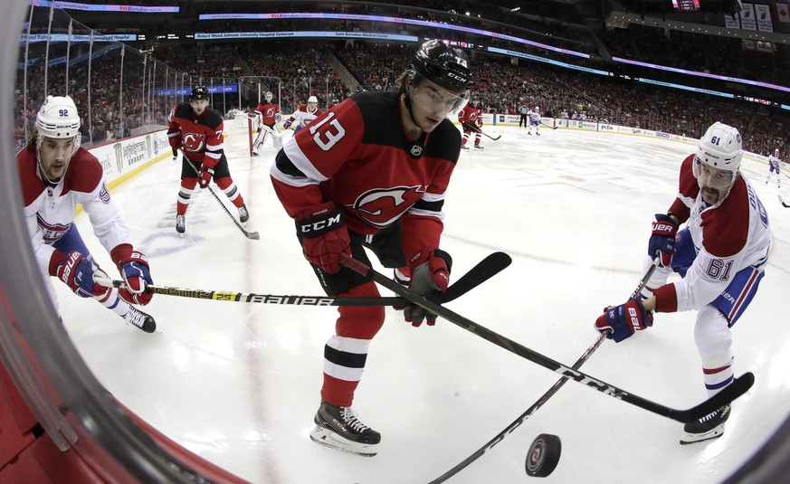 New Jersey Devils center Nico Hischier (13), of Switzerland, competes for the puck with Montreal Canadiens center Jonathan Drouin (92) and defenseman Xavier Ouellet (61), of France, during the first period of an NHL hockey game, Wednesday, Nov. 21, 2018, in Newark, N.J. (AP Photo/Julio Cortez)
