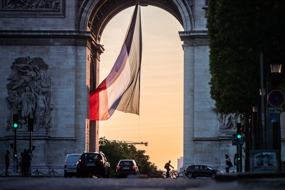 epa08448766 The national flag of France waves next to the Arc de Triomphe in Paris, France, 27 May 2020 (issued 28 May 2020). France has begun a gradual lifting of COVID-19 lockdown restrictions in an effort to restart its economy and help people get back to their daily routines. People spend time in open parks and public spaces while restaurants and bars remain closed.  EPA/MOHAMMED BADRA