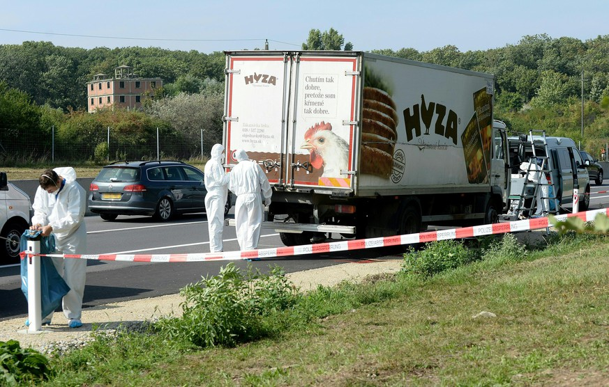epa04900497 Forensic experts investigate a truck in which refugees were found dead as it stands on freeway autobahn A4 between Parndorf and Neusiedl, Austria, 27 August 2015. According to reports, some 50 refugees were found dead in the lorry parked at the autobahn. It cannot be confirmed if the dead suffocated in the truck, as some media have reported. The lorry was discovered by highway workers who called police. The driver has disappeared, according to media reports.  EPA/ROLAND SCHLAGER