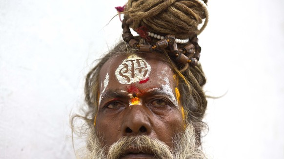 A Sadhu or Hindu holy man, written 'Ram', a name of a Hindu lord, on his forehead, offers prayer at the Umananda, a river island in the Brahmaputra that houses a Shiva temple, during Shivratri festival in Gauhati, India, Wednesday, Feb. 14, 2018. Shivaratri, or the night of Shiva, is dedicated to the worship of Lord Shiva, the Hindu god of death and destruction. (AP Photo/Anupam Nath)