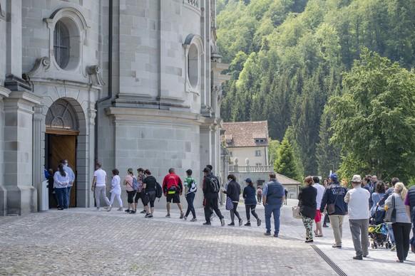 Glaeubige stehen schlange vor der Kirche und halten sich an die Corona-Pandemie Sicherheitsregeln des Bundes waehrend einer Pfingstmesse in der Klosterkirche von Einsiedeln am Pfingstsonntag 31. Mai 2020 in Einsiedeln. (KEYSTONE/Urs Flueeler).