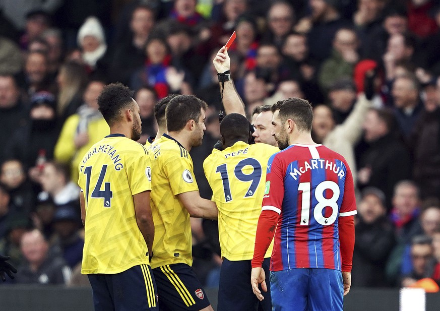 Referee Paul Tierney shows Pierre-Emerick Aubameyang, left, a red card following a VAR review , during the English Premier League soccer match between Crystal Palace and Arsenal, at Selhurst Park, in London, Saturday,  Jan. 11, 2020. (Tess Derry/PA via AP)