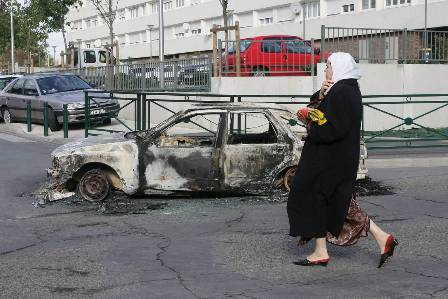 A resident walks past the remains of a car which was set on fire overnight in the north eastern Paris suburb of Aulnay sous Bois, Thursday 03 November 2005. French Prime Minister Dominique de Villepin said Thursday a return of order was his government's priority after a seventh consecutive night of rioting in the ghettoes of suburban Paris.  EPA/TRAVERS / LE FLOCH FRANCE OUT *** Local Caption *** 518930