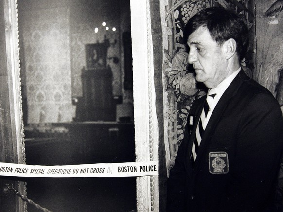 In this March 21, 1990 photo, a security guard stands outside the Dutch Room of the Isabella Stewart Gardner Museum, where robbers stole more than a dozen works of art in an early morning robbery in Boston. It remains the most tantalizing art heist mystery in the world. In the early hours of March 18, 1990, two thieves walked into Boston's elegant Isabella Stewart Gardner Museum disguised as police officers and bound and gagged two guards using handcuffs and duct tape. For the next 81 minutes, they sauntered around the ornate galleries, removing masterworks including those by Rembrandt, Vermeer, Degas and Manet, cutting some of the largest pieces from their frames. Now, 20 years later, investigators are making a renewed push to recover the paintings.  (AP Photo)