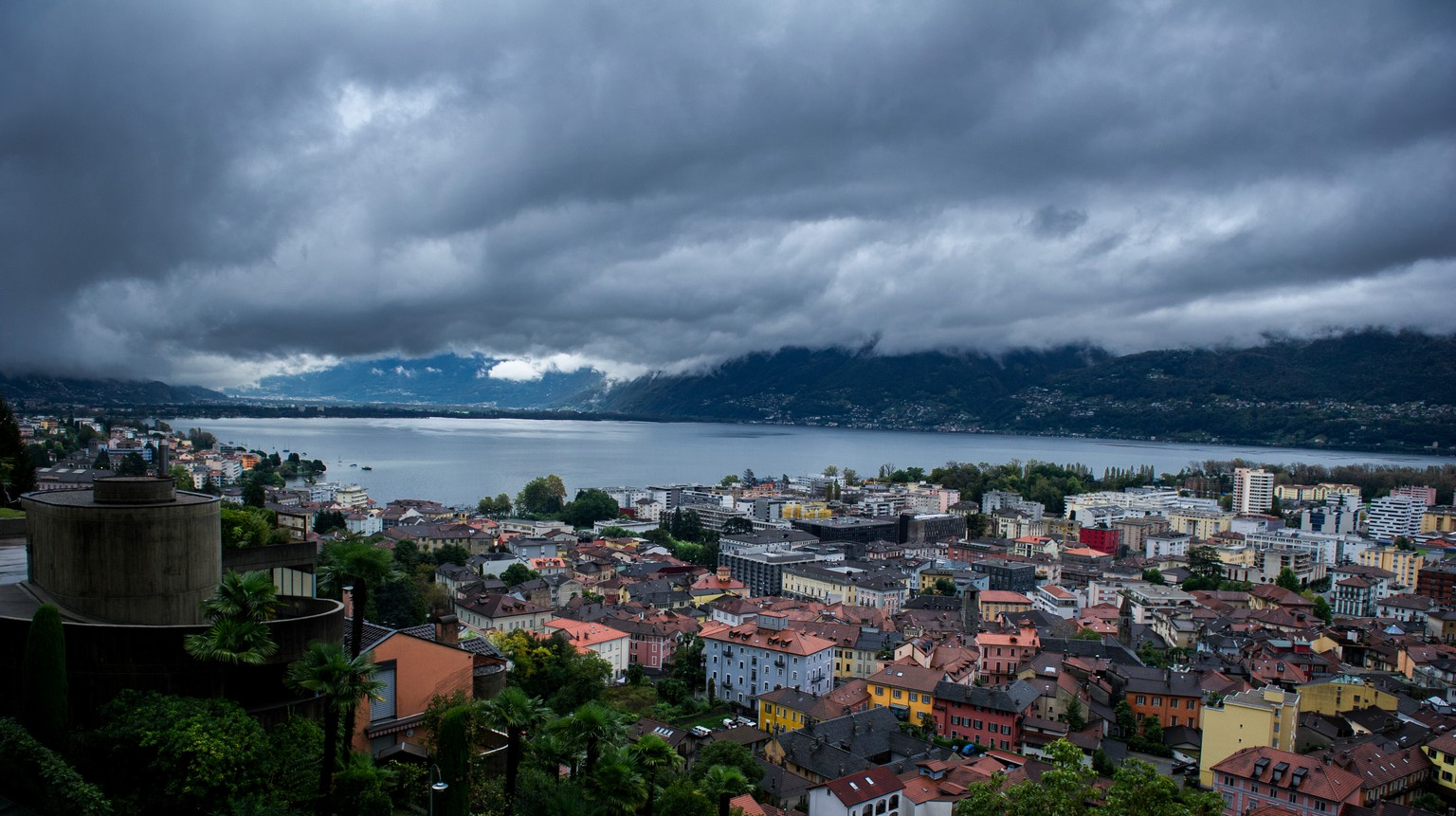 Dunkle Wolken ueber Locarno, aufgenommen am Montag, 13. Oktober 2014. Das Tessin wird derzeit von heftigen Regenfaellen heimgesucht. Gebietsweise seien im Tessin von Sonntag auf Montag bis zu 100 Liter Regen pro Quadratmeter gefallen, erklaerte MeteoSchweiz. In den kommenden 24 Stunden sei noch einmal die gleiche Regenmenge zu erwarten.(KEYSTONE/Ti-Press/ Carlo Reguzzi)