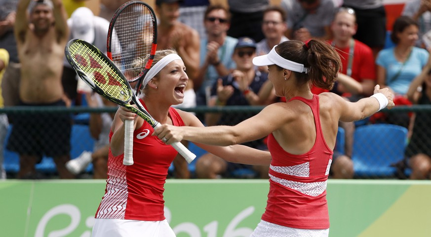 epa05465115 Timea Bacsinszky (L) and Martina Hingis of Switzerland celebrate after winning the women's second round doubles match against Bethanie Mattek-Sands and Coco Vandeweghe of USA of the Rio 2016 Olympic Games Tennis events at the Olympic Tennis Centre in the Olympic Park in Rio de Janeiro, Brazil, 08 August 2016.  EPA/PETER KLAUNZER