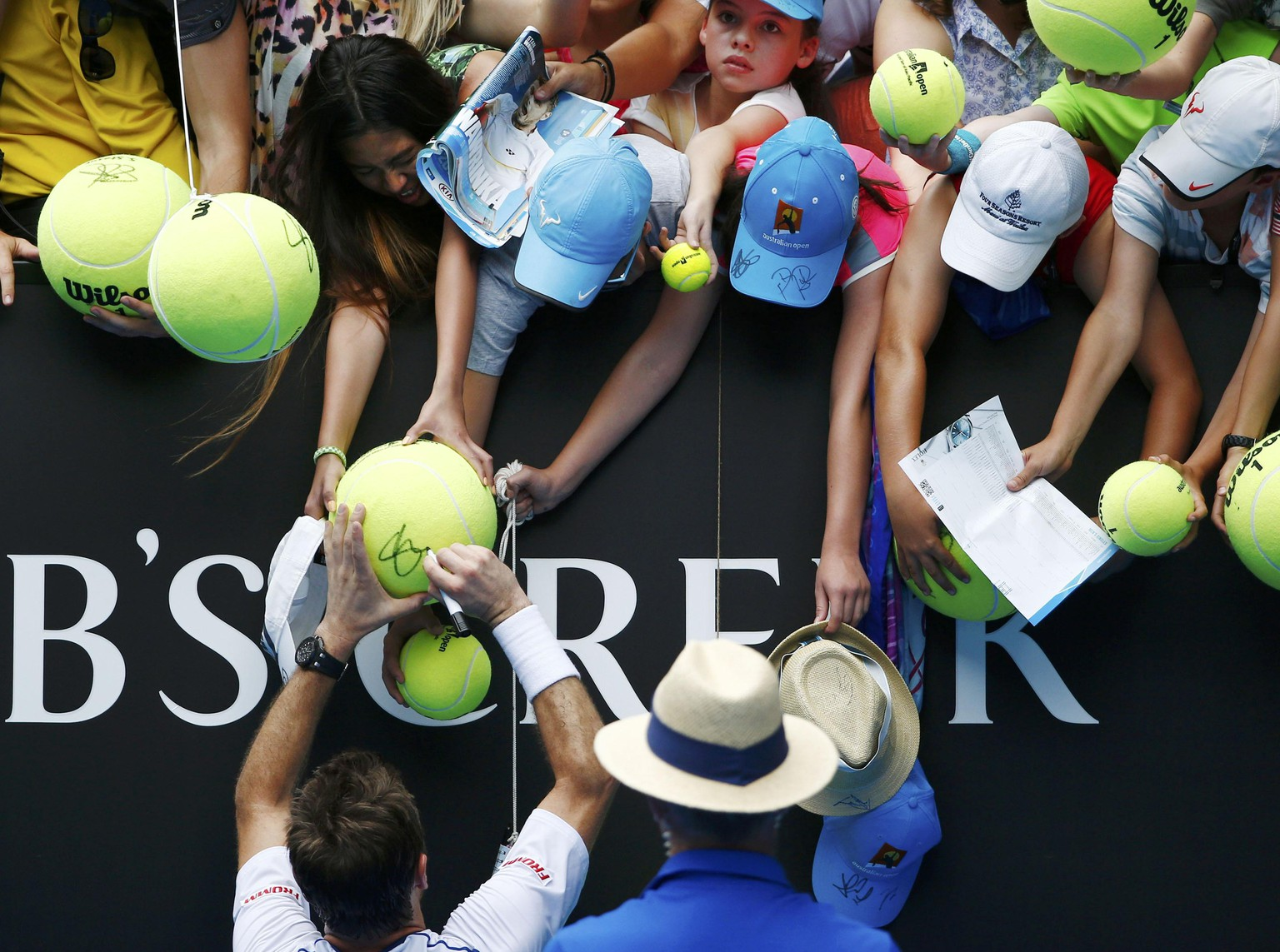 Stan Wawrinka (bottom L) of Switzerland signs autographs after defeating Marsel Ilhan of Turkey to win their men's singles first round match at the Australian Open 2015 tennis tournament in Melbourne January 20, 2015. REUTERS/Athit Perawongmetha (AUSTRALIA  - Tags: SPORT TENNIS)